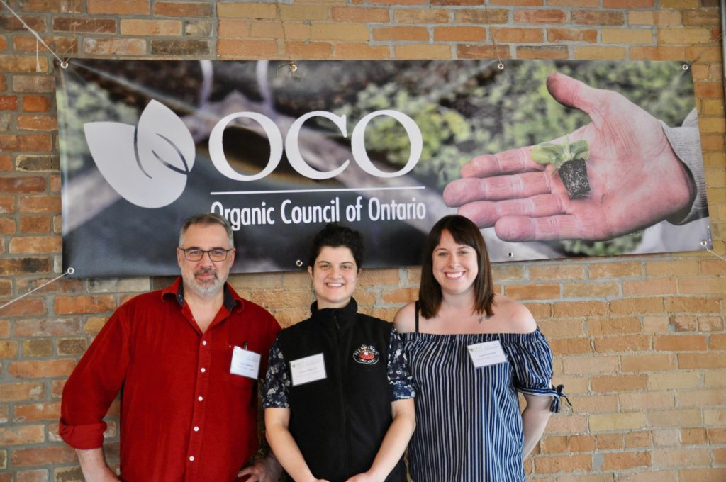 Glenn Valliere, Lauren Stallard, and Laura Mitchell standing under the OCO banner
