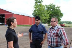 Jenn Pfenning engaged in conversation with 2 HUMA representatives on the farm
