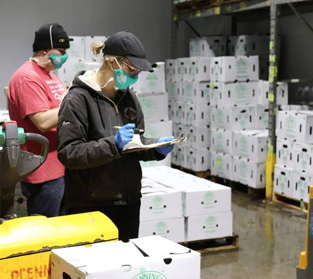 Staff working in warehouse wearing face masks and gloves.