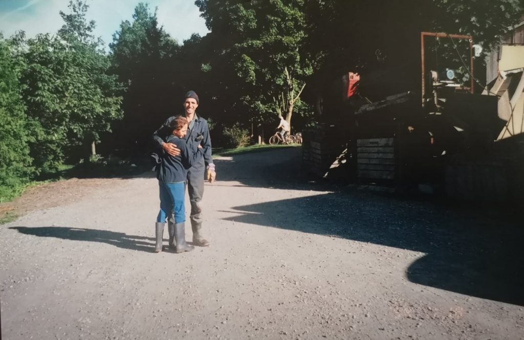 Young Erika and Wolfgang hugging in their rubber boots on the farm.